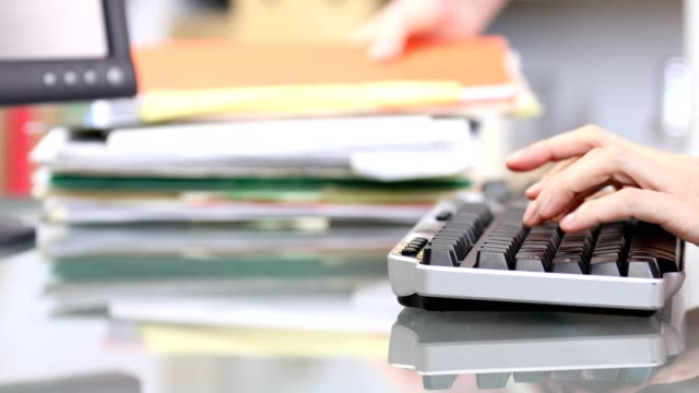 office worker typing on computer keyboard, stacking files. - schedario documento video stock e b–roll