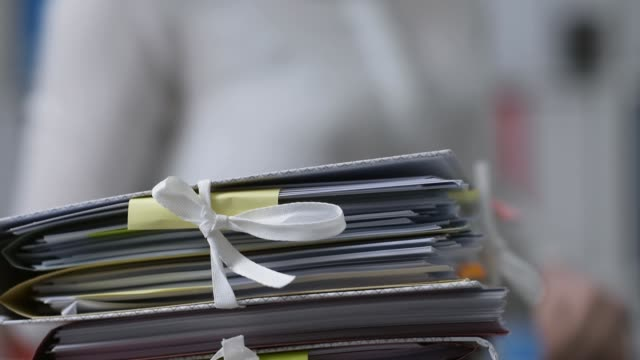 Office workers adding files on stacks of paperwork Office workers adding files on stacks of paperwork: work overload and management concept large group of objects stock videos & royalty-free footage