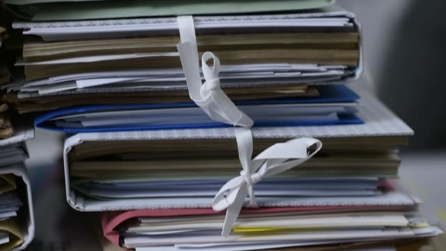 Office workers adding files on stacks of paperwork