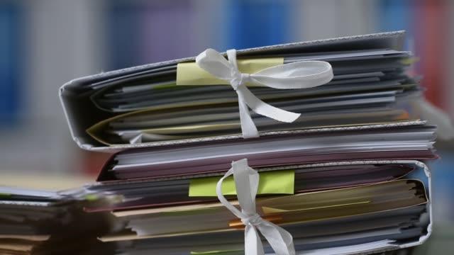 vídeos de stock e filmes b-roll de office workers adding files on stacks of paperwork - dossier