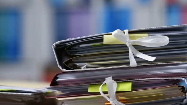 Office workers adding files on stacks of paperwork video