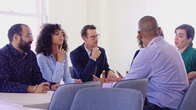 Office Workers Brainstorming A diverse group of men and women of varying ages and ethnicities are sitting around a conference table in a bright, modern office building. One of the women yawns and looks around. yawning stock videos & royalty-free footage