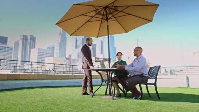 büroangestellte genießen treffen am dachgarten auf sonnigen tag in los angeles - dachgarten videos stock-videos und b-roll-filmmaterial