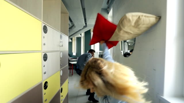 Office workers having fun in their free time running down corridor and throw pillows video