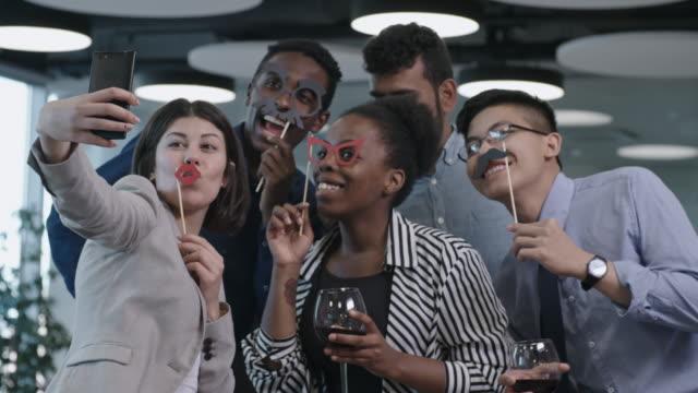 vídeos de stock, filmes e b-roll de trabalhadores de escritório, tendo selfie engraçado na festa corporativa - festa da empresa