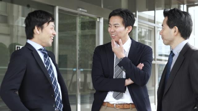 オフィスの仕事仲間をお連れになり、スタンド - ビジネスマン 日本人点の映像素材/bロール