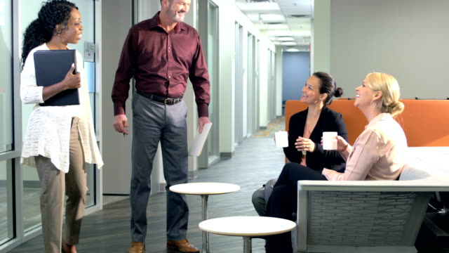 office workers walk down hallway, greet coworkers - pausa caffè video stock e b–roll