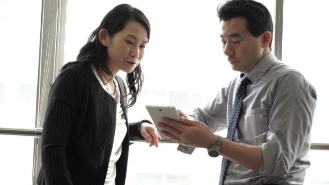 vídeos de stock e filmes b-roll de trabalhadores de escritório trabalhando juntos no tablet pc - senior business woman tablet