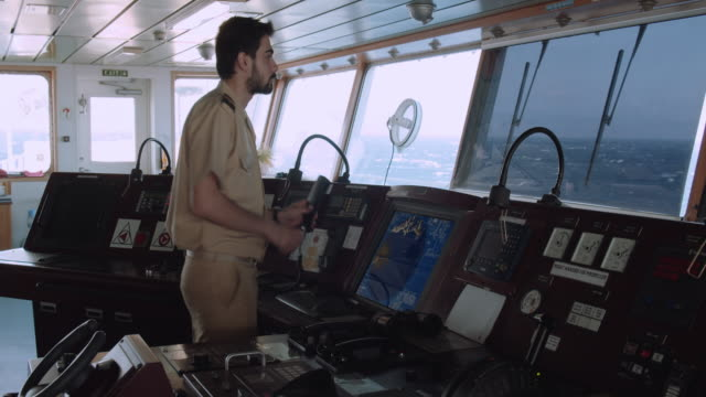 officer is calling the other ship by radio - natante industriale video stock e b–roll
