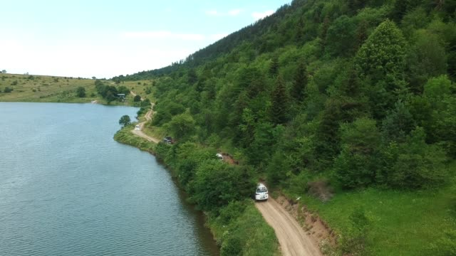off-road cars are going near the lake - fianco a fianco video stock e b–roll
