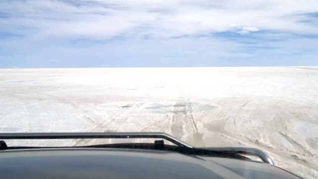 Off-road vehicle driving on Salar de Uyuni, Bolivia Off-road vehicle driving on Salar de Uyuni, Bolivia salt flat stock videos & royalty-free footage