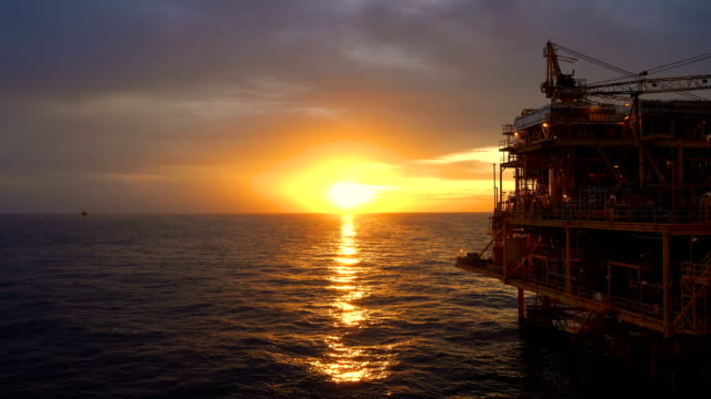 Offshore oil and gas platform, Central processing platform in sunset time produced raw gases and condensate or crude oil then sent gas to onshore refinery video