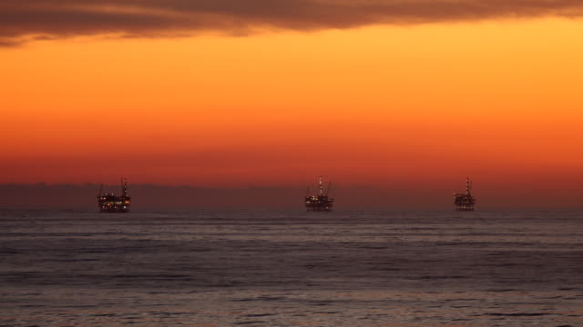 Offshore Oil Rig Drilling Platforms at Sunset video
