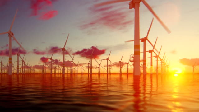 offshore windmills with technician boat at sunset, panning - sustainability video stock e b–roll