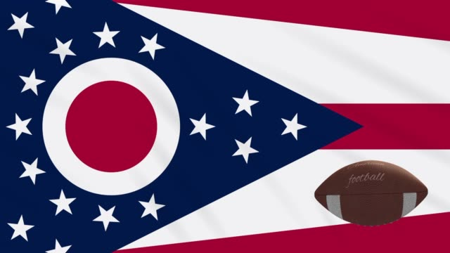 ohio flag waving and american football ball rotates, loop - columbus day filmów i materiałów b-roll