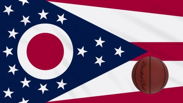 ohio bayrağı sallayarak ve basketbol topu döner, döngü - columbus day stok videoları ve detay görüntü çekimi