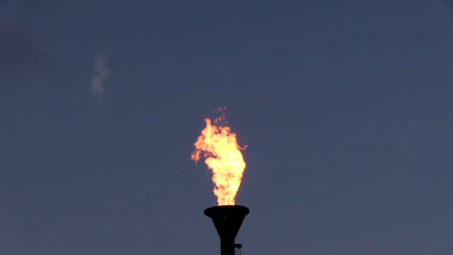 stockvideo's en b-roll-footage met oil burning torch against a sunset sky - fakkel