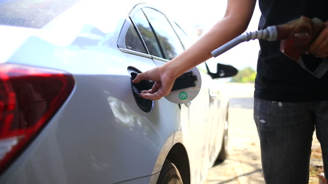 Oil crisis Man filling a car gas tank while vehicle at gas station. refueling stock videos & royalty-free footage