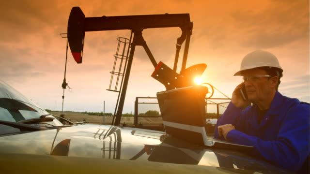Oil field worker at oil pump jack A top level management employee works on a laptop and with a truck at an oil pump jack site at sunset. He is wearing safety personal protection equipment including safety glasses, coveralls and a hardhat. oil industry stock videos & royalty-free footage