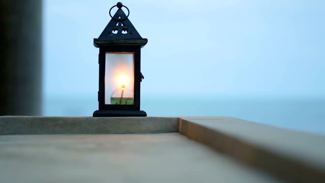 Oil lamp at twilight on balcony. video