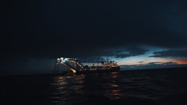 oil producing boat lighted up in night sea waters with last sun beams on horizon - cartello economico video stock e b–roll