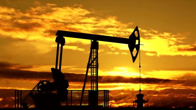 Oil pump jack against sunset video
