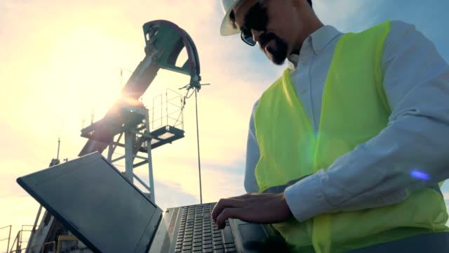 stockvideo's en b-roll-footage met olie pompen werknemer op een zonsondergang achtergrond, close-up. - olieraffinaderij