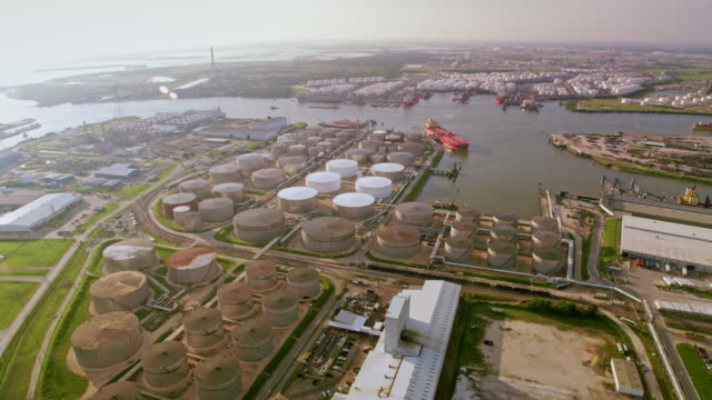 AERIAL Oil refinery storage tanks and cargo ships docked on the river in Houston, TX