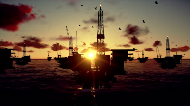 Oil rigs in ocean, time lapse sunset video