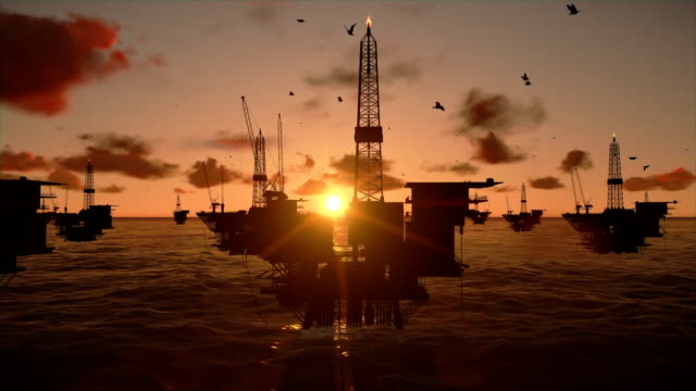 Oil rigs in ocean, timelapse sunset video