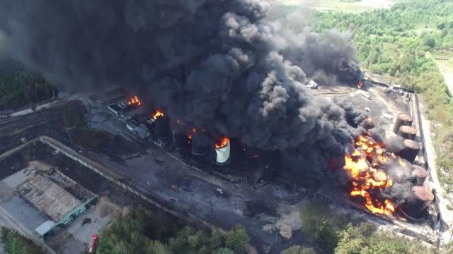 vídeos de stock, filmes e b-roll de fogo do armazenamento de óleo. a fazenda do tanque está queimando, fumaça preta - gasolina