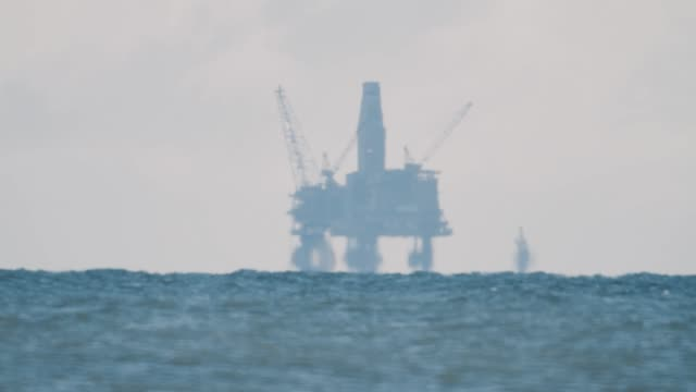 oil water platform silhouette on horizon in hazy air over sea surface - opec video stock e b–roll