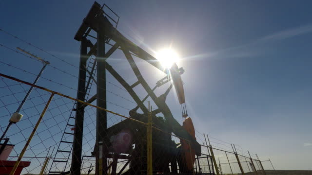 Oil Well Rig Pump against Sun 4K video