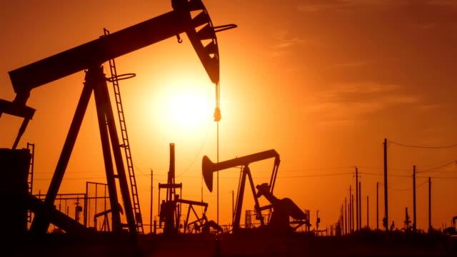vídeos de stock e filmes b-roll de poços de petróleo no nascer do sol - combustível fóssil