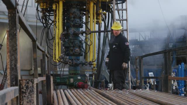 vídeos de stock, filmes e b-roll de trabalhadores do campo de petróleo rig up tubo de perfuração em uma plataforma alta, metal em um local de perfuração de óleo e gás em uma manhã fria de inverno - equipamento