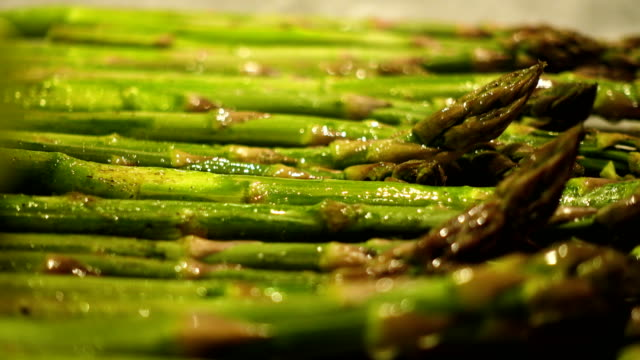 oiling fresh green asparagus stems with the brush before baking close up - alla griglia video stock e b–roll