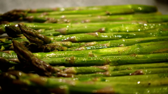 oiling fresh green asparagus stems with the brush before baking close up