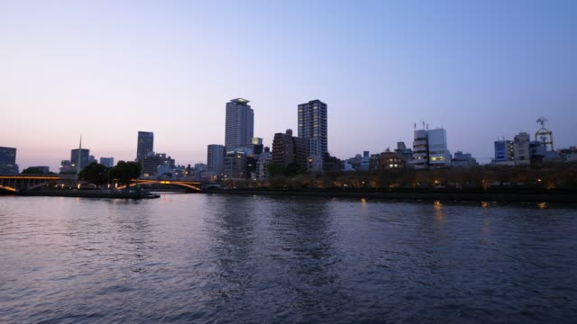 vídeos de stock e filmes b-roll de okawa river and tenjin bridge panorama at blue hour, scenic views of osaka city - margem do rio