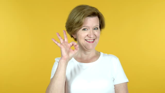 Okay Sign by Old Woman Isolated on Yellow Background Okay Sign by Old Woman Isolated on Yellow Background satisfaction stock videos & royalty-free footage