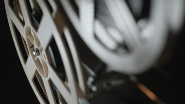 古い 8 mm フィルム映写がスモーキーの部屋で夜に遊んで。フィルム回転リールのクローズ アップ - 映画用カメラ点の映像素材/bロール