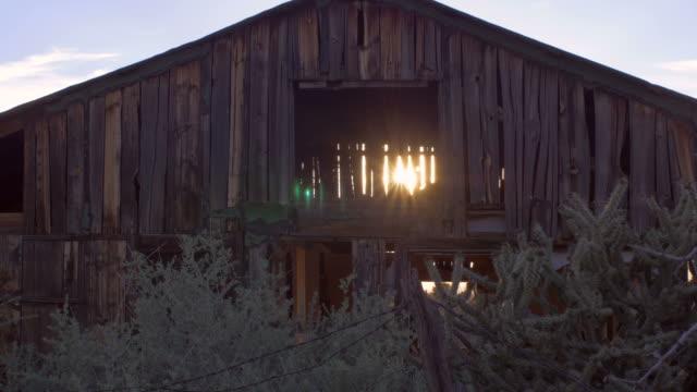 old abandoned barn with sun light streaming through open beams - ahır stok videoları ve detay görüntü çekimi