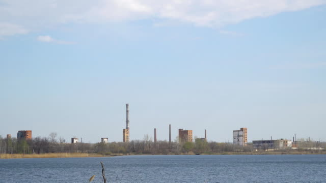 Old Abandoned chemical factory with chimneys on the banks of river video