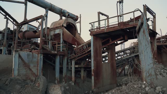 Old abandoned industrial rusty metal mining equipment construction at ore and stone quarry video
