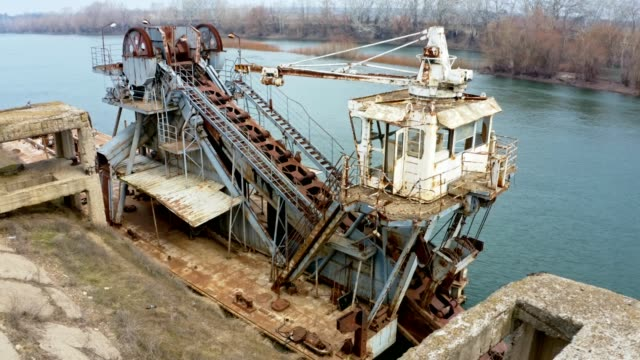 Old abandoned mining machine on the river