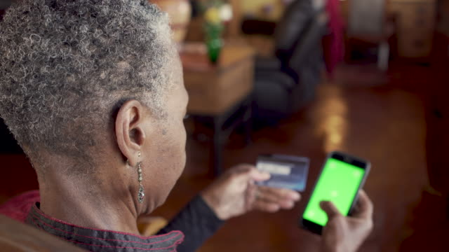 Old African American woman shopping with a credit card and a smart phone