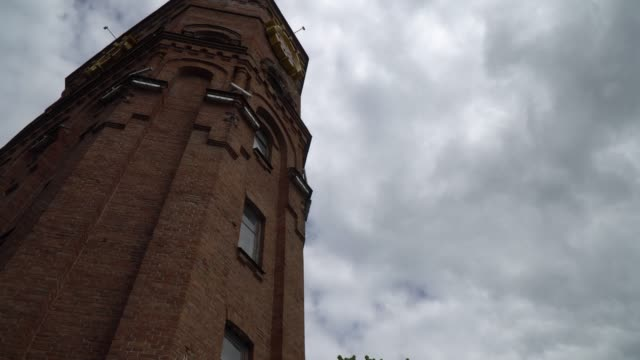 Old ancient tower from red brick, against overcast sky.
