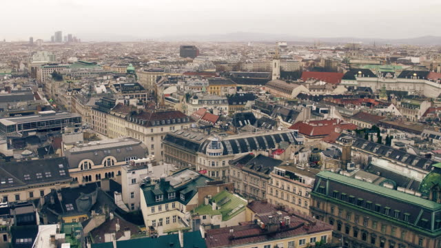 old and modern buildings' roofs in vienna on a cloudy day, austria. warm colors fullhd overview pan video - австрия стоковые видео и кадры b-roll