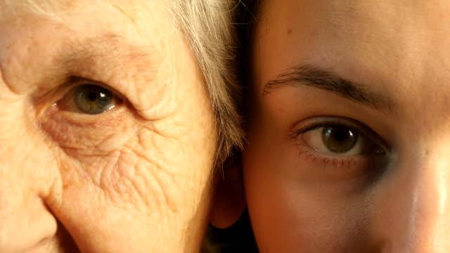 vidéos et rushes de vieux et jeune eye-grand-mère et petite-fille ensemble à la recherche de l'appareil photo - peau humaine