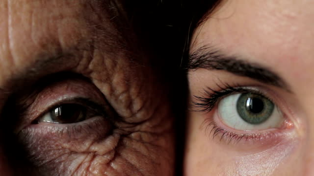 old and young eye - Grandmother and granddaughter looking together at camera video
