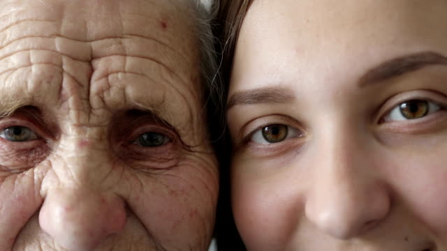 Old and young face. Grandmother and granddaughter looking together at camera. video